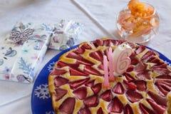 Födelsedagjordgubbekaka och gåvor på den vita bordduken royaltyfria bilder