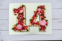 Födelsedagkaka i form av numret fjorton arkivfoto