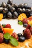 Födelsedagkaka med bär av druvor och kumquaten på vit bakgrund Bild för en meny eller en konfektkatalog Fotografering för Bildbyråer