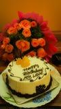 Födelsedagkaka med blomman och klockan Fotografering för Bildbyråer
