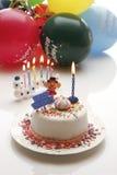 Födelsedagkaka med bränningstearinljus och ballonger fotografering för bildbyråer