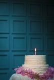Födelsedagkaka med bränningstearinljuset på blå bakgrund; Arkivfoto