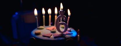 Födelsedagkaka med brinnande stearinljus och ålder 6 stearinljus i den mörka bakgrunden med godisar i dekor arkivbild