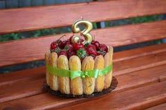 Födelsedagkaka med jordgubbar och körsbär på en träbakgrund royaltyfri foto