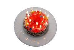 Födelsedagkaka med tända stearinljus på plattan Arkivfoton