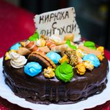 Födelsedagkakan dekorerade med ett kex med inskriften KIRILL, LYCKLIG FÖDELSEDAG Arkivbild