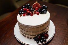 Födelsedagkakan dekorerade med nya frukter på den vita plattan Arkivfoto