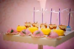 Födelsedagkakor Detalj av en efterrätttabell - färgrika kakor med den rosa födelsedagtopperen royaltyfri foto