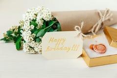 Födelsedagkort med den guld- närvarande asken med Glass hjärta Vita små blommor för bukett i brunt hantverkpapper med rad Trävit Fotografering för Bildbyråer
