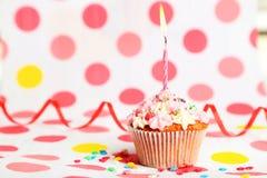 Födelsedagmuffin med den smörkräm och stearinljuset på färgrik bakgrund Royaltyfria Bilder