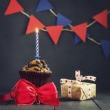 Födelsedagmuffin med en stearinljus på en mörk bakgrund Lyckliga lyckliga födelsedagar vykort Lyckönskan Arkivfoton