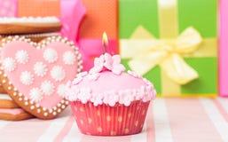 Födelsedagmuffin med stearinljuset och gåvor Arkivfoton