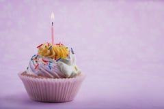 Födelsedagmuffin med stearinljuset, på rosa färgerna Arkivbild