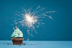 Födelsedagmuffin med tomteblosset på en blå bakgrund royaltyfria foton