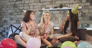 Födelsedagparti som firar om attraktiva damer för en tonåring i ett modernt sovrum som dricker champagne som drömmer och ler arkivfilmer