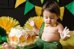 Födelsedagpojke med smutsiga händer från kakanärbild royaltyfri fotografi