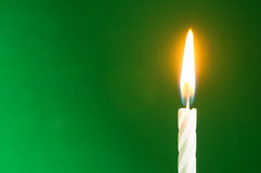 Födelsedagstearinljuset på en grön bakgrund Arkivfoto