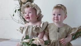 Födelsedagsystrar i klänningar som sitter på photoshoot i studio på bakgrund av väggen med dekoren lager videofilmer