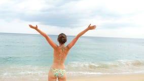 Följ den unga lyckliga kvinnan som kör på stranden till havet och, lyftte händer H?rlig flicka som joggar p? sandig kust till lager videofilmer