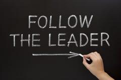 Följ ledare på blackboarden Arkivbild