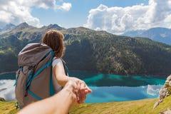 Följ mig begreppet av den unga kvinnan med en stor ryggsäck i bergen som ser sjön arkivbild