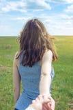 Följ mig, den attraktiva brunettflickan som rymmer handen av blytaket i ett rengöringgräsplanfält, stäpp med moln royaltyfria bilder