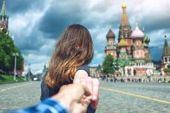 Följ mig, den attraktiva brunettflickan som rymmer handen, leder till den röda fyrkanten i Moskva Ryssland royaltyfri fotografi