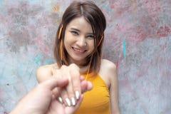 Följ mig För innehavpojkvän för ung kvinna hand med den lyckliga framsidan Le lyssnande musik för asiatisk flicka med headphonen  royaltyfria foton