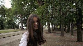 Följ mig flickabegreppet Den unga nätta lyckliga studentmodellen som in ler och går, parkerar stock video