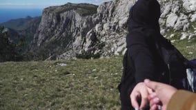 Följ mig Ledande man för kvinna som rymmer hans hand till överkanten av berget på sommardag stock video