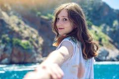 Följ mig, leder den attraktiva brunettflickan som rymmer handen, till bergen och det blåa havet fotografering för bildbyråer