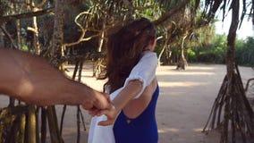 Följ som mig, drar skottet av den unga kvinnan hennes pojkvän på havskusten Hand och spring för flicka hållande manlig på tropisk stock video