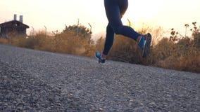 Följ till fot av ung flickaspring på landsvägen Kvinnligt ben som joggar i natur Sportig aktiv livsstil långsam rörelse stock video