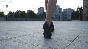 Följ till kvinnliga ben i skor för höga häl som går i den stads- gatan Fot av den unga affärskvinnan, i hög-heeled arkivfilmer