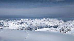 Följande spår för skidåkare som leder in i dalen över untracked snö fi Royaltyfri Bild
