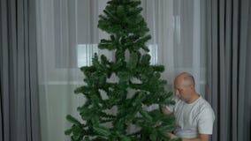 Följd för effekt Timelapse för snabb rörelse Att forma sörjer det vintergröna granträdet för jul Vuxen caucasian man hemma lager videofilmer