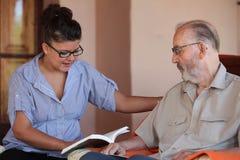 Följe eller granchild som läser till pensionären eller farfadern Arkivfoton