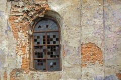 Fönster av en gammal övergiven byggnad, med brutet exponeringsglas som täckas med lösa druvor royaltyfri fotografi