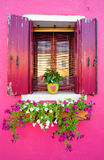 Fönster av ett crimson hus Arkivfoto