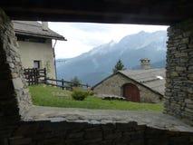 Fönster av stenen som förbiser taket av stenhuset med moutainsna trots allt Val av Suza, Italien Arkivfoton
