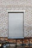 Fönster bricked upp Fönstret stigas ombord upp med den gråa lägenheten kritiserar En grå tegelstenvägg med ett stigit ombord-upp  arkivfoton