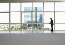 Fönster för affärsmanLooking Out Of kontor arkivfoto