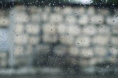 Fönster i förgrunden av inre av en bil med droppar av vatten och en bakgrundsvägg med stora tegelstenar royaltyfri bild