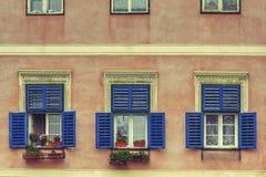 Fönster med öppna slutare och blommor Arkivfoto