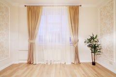 Fönster med beigagardiner i enkelt rum Arkivbild