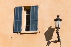 Fönster med blåttslutare och den gamla streetlampen Arkivfoto