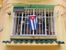 FÖNSTER MED DEN KUBANSKA FLAGGAN, HAVANNACIGARR, KUBA Arkivfoto