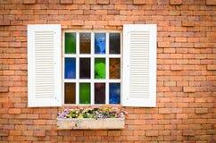 Fönster med den röda tegelstenväggen. arkivbilder