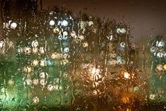 Fönster med droppar av nattregn i en stad Royaltyfri Foto