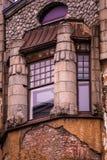 Fönster med kolonner i det gamla huset med den brutna fasaden Arkivfoton